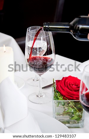 man and woman in restaurant for dinner drinking red wine and smiling - stock photo