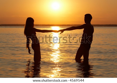 man and woman in water hold each other hand - stock photo