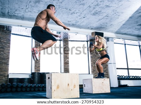 Man and woman jumping on fit box at gym - stock photo