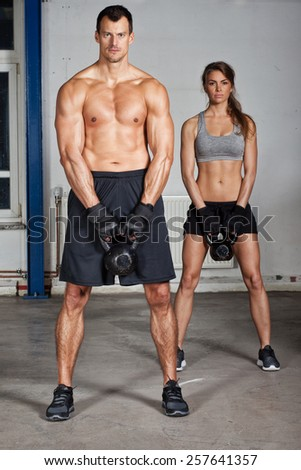 man and woman lifting kettle bell crossfit - stock photo
