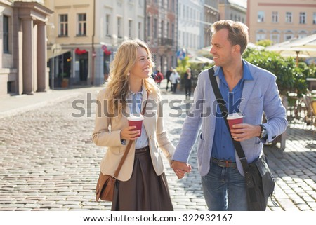 Man and woman looking at each other and holding hands - stock photo
