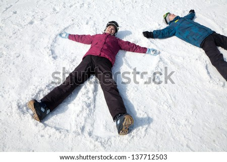 Man and Woman Lying on the Snow Making Snow Angel - stock photo