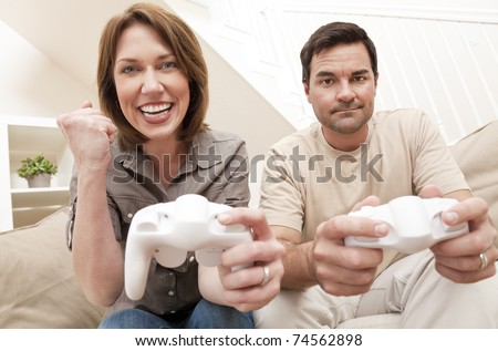 Man and woman married couple having fun playing computer console game together, the woman is celebrating winning the man is upset losing - stock photo