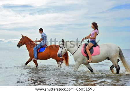 Man and woman on horseback - stock photo