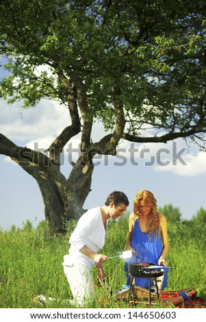 man and woman on picnic in green grass - stock photo