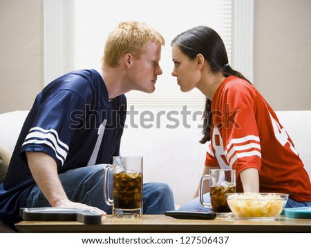 Man and woman on sofa staring at each other angrily - stock photo