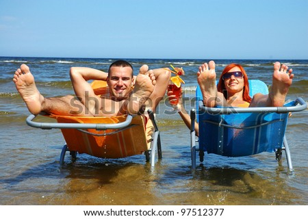 Man and woman on the  deck-chair - stock photo