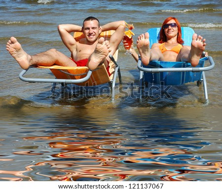 Man and woman on the deck-chair to the beach - stock photo