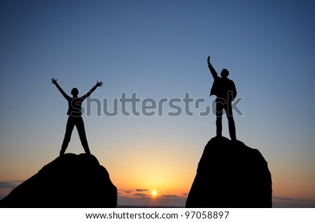 man and woman on top of a mountain on the background of the sunset - stock photo