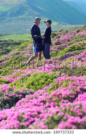 Man and woman on vacation in the mountains. Couple in love among the flowers. Bushes blooming pink rhododendron. Carpathian mountains, Ukraine - stock photo