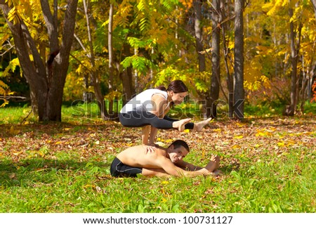 Man and woman practice Yoga tittibhasana on pashchimottanasane pose in forest - stock photo