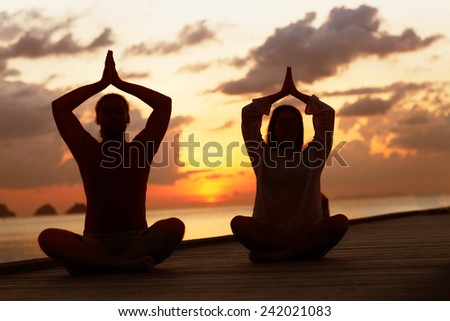 man and woman practicing yoga at sunset  - stock photo