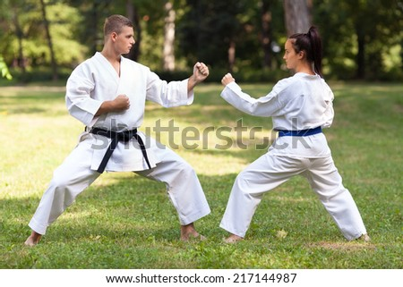 Man and woman practicing zenkutsu dachi stance - stock photo