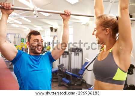 Man and woman reaching up to monkey bars at a gym - stock photo