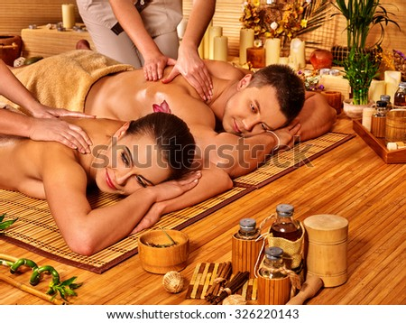 Man and woman relaxing in bamboo  spa interior on wooden floor. - stock photo
