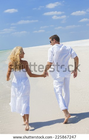 Man and woman romantic couple in white clothes running holding hands on a deserted tropical beach with bright clear blue sky - stock photo