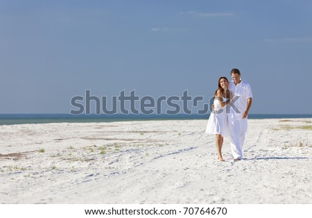 Man and woman romantic couple in white clothes walking and laughing together on a deserted tropical beach with bright clear blue sky - stock photo