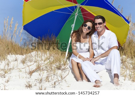 Man and woman romantic couple wearing sunglasses under a multi colored sun umbrella or parasol on a beach - stock photo