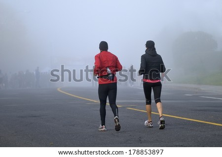 Man and woman running before the course - stock photo