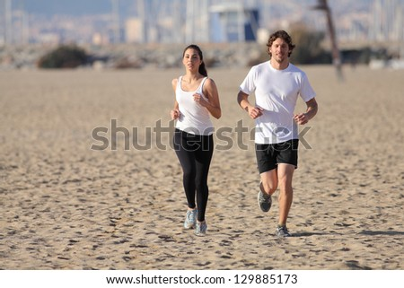 Man and woman running on the beach with an unfocused background - stock photo