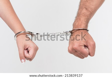 Man and woman's hands handcuffed together concept of love, relationship, romance, sex, crime, punishment, prison isolated on white - stock photo