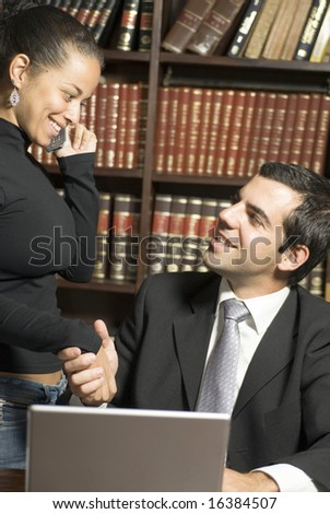Man and woman shake hands over laptop. They are smiling at each other while she is on the cellphone. Vertically framed photo. - stock photo