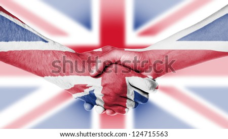 Man and woman shaking hands, arms wrapped in the flag the UK - stock photo