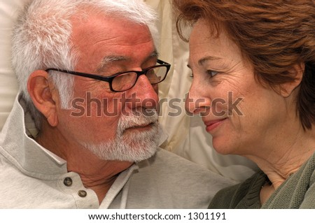 Man and woman share a private bedroom moment - stock photo