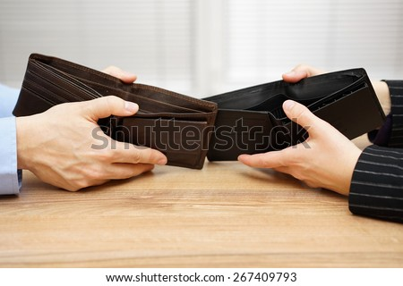 man and woman shows empty wallet to each other - stock photo