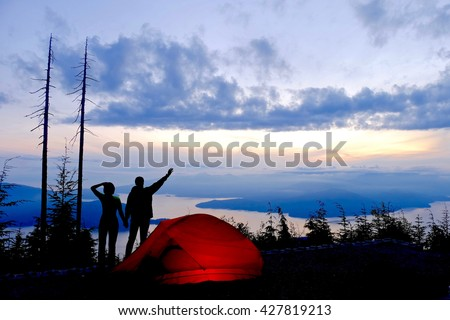 Man and Woman Silhouette by Red Tent with View of Ocean and Islands at Sunrise.  View of Bowen Island from Bowen Lookout. Cypress Provincial Park, Vancouver, British Columbia, Canada  - stock photo