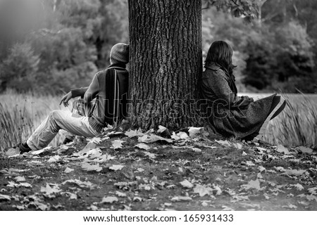 Man and woman sitting in park after quarrel  - stock photo