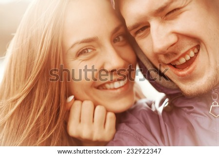 Man and woman smiling and taking pictures of themselves - stock photo