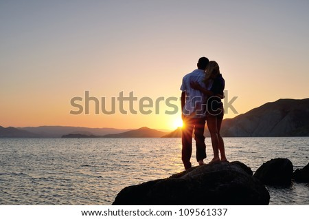 Man and woman standing arm in arm on a rock by the sea and watching the sunset - stock photo