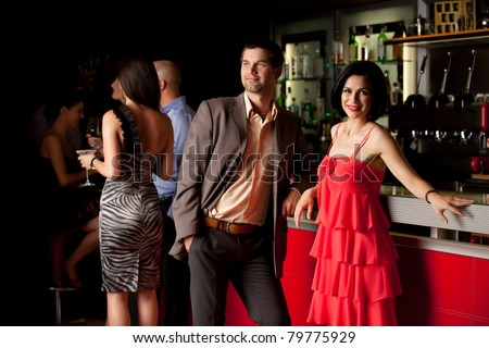 man and woman standing beside nightclub bar smiling - stock photo