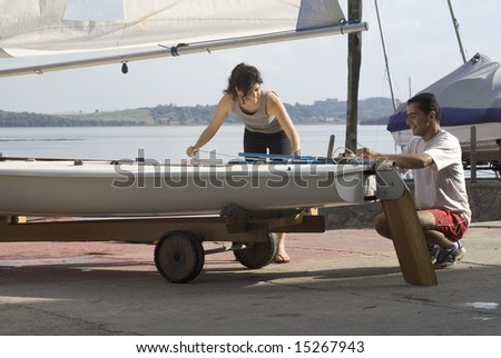 Man and woman standing next to sailboat getting ready to sail. Horizontally framed photo. - stock photo