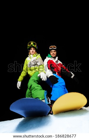 Man and woman standing on snowboards at night - stock photo