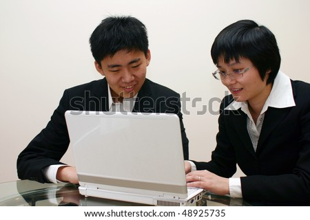 Man and woman use laptop together. - stock photo