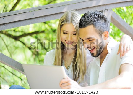 Man and woman using laptop outdoors - stock photo
