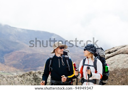 Man and woman walking in Himalaya mountains in Nepal, sport in nature. Young people traveling in Asia, trekkers on trail in wilderness. - stock photo