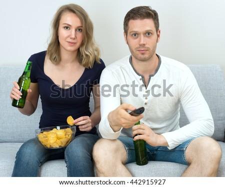 Man and woman watching sports match on tv. - stock photo