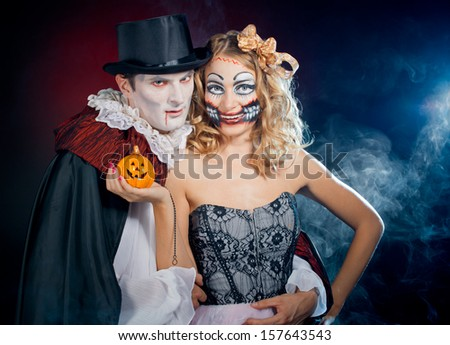 man and woman  wearing  as  vampire and Chucky doll. Halloween - stock photo