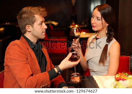 Man and woman with a glass of wine looking lovingly into the eyes - stock photo