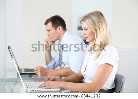 Man and woman working in the office on laptop computer - stock photo