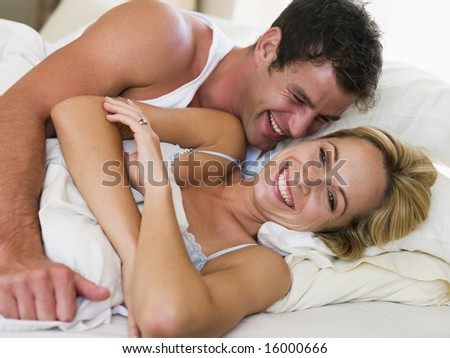 man and women awake in bed laughing - stock photo