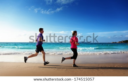 Man and women running on tropical beach at sunset  - stock photo