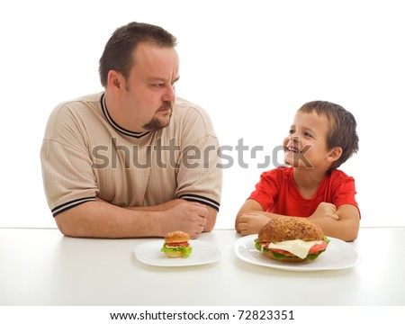 Man and young boy humorously rival over food - stock photo