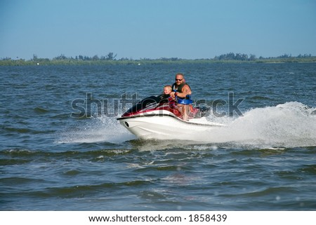 Man and young boy on jet ski - stock photo