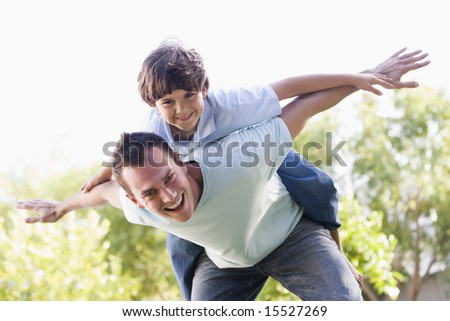 Man and young boy outdoors playing airplane smiling - stock photo
