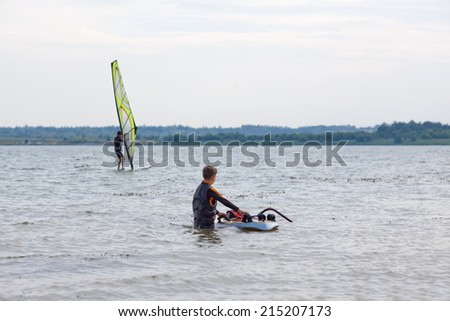 Man and young boy practicing windsurfing moves on a surfboard on seashore - stock photo