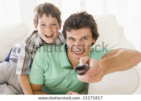 Man and young boy with remote control smiling - stock photo